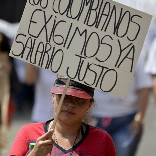 Una mujer sostiene una pancarta con la que pide un salario justo durante una manifestación contra la política económica del entonces presidente Juan Manuel Santos, el 25 de enero de 2016, en Cali, Colombia.