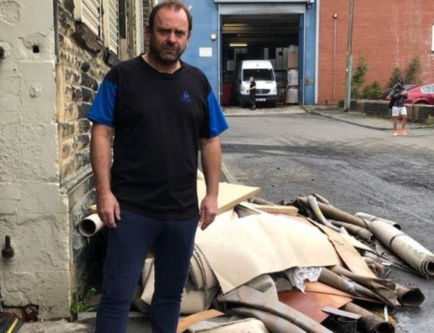 Carpet shop owner Philip Holt with carpet ruined by flood water