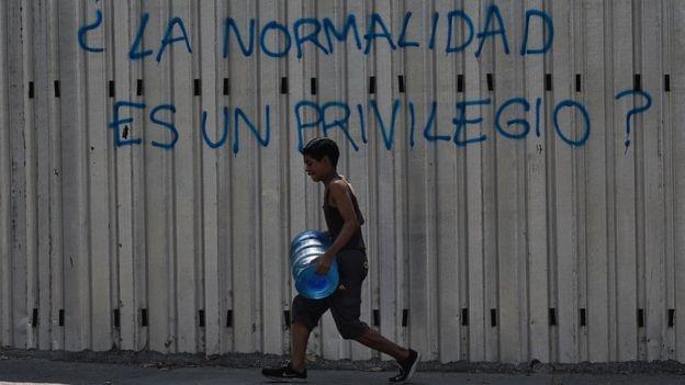 Jovem carrega galão de água em Caracas