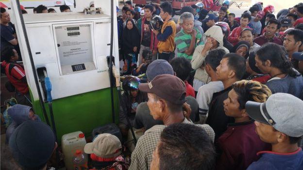 People crowd around a petrol pump in Palu