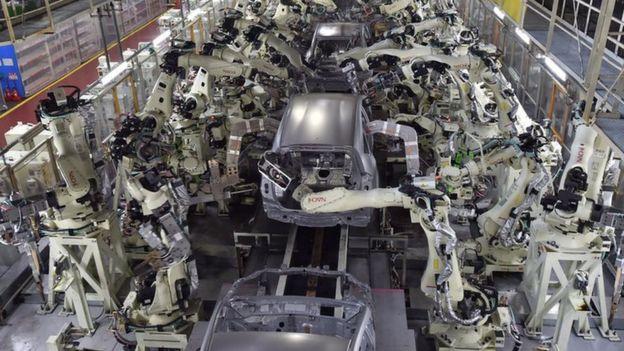 Robots welding car bodies in factory