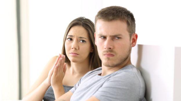 Mujer pidiendo perdón a un hombre enfadado.