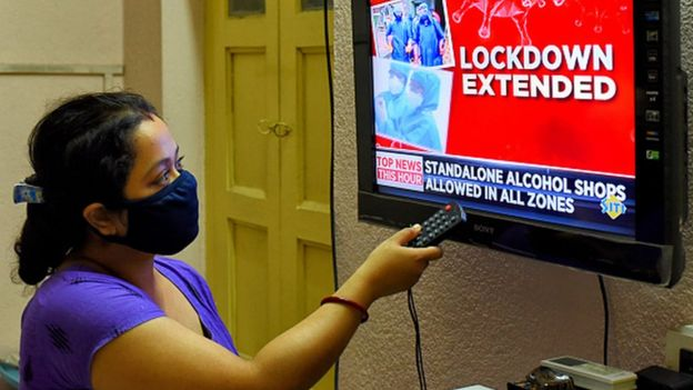 A woman watches news of extension of lockdown in India