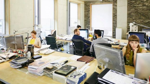 موظفون في مكتب العمل يجلسون أمام شاشات الكمبيوتر