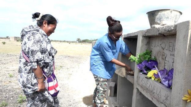 Sonia Bermúdez ayuda a una indígena Wayuu venezolana a enterar a su hermano en el cementerio Gente Como Uno, en la ciudad colombiana de Riohacha, el 30 de agosto de 2018.