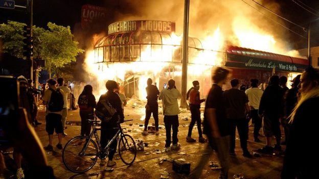 Manifestantes se reúnen para ver arder una licorería