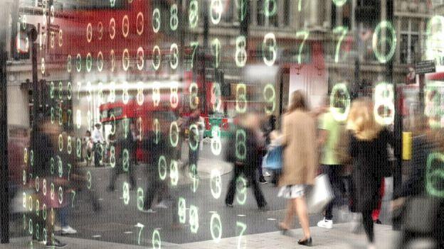 Pessoas diante de um painel numérico