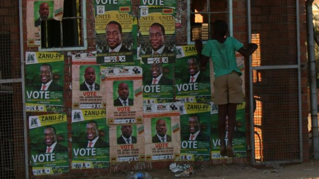 A boy plays next to election posters at White City Stadium where Zimbabwe's President Emmerson Mnangagwa escaped unhurt after an explosion rocked the stadium, in Bulawayo, Zimbabwe, June 23, 2018.