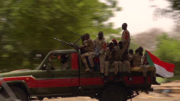 Rapid Support Forces militia are seen driving along the road, holding guns