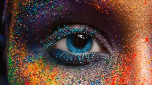 The eye of a woman and her face painted in different colors.