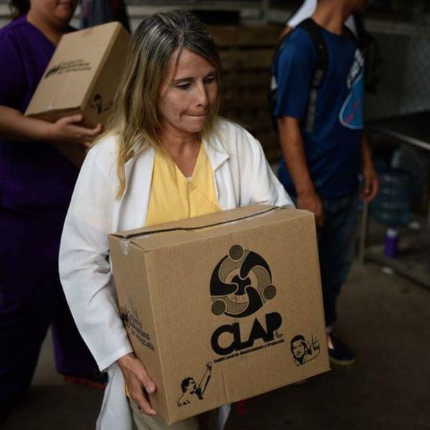 En Venezuela, el gobierno distribuye las polémicas cajas de alimentos subsidiados CLAP a través de comités locales.