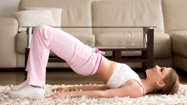Mujer haciendo gimnasia en casa.