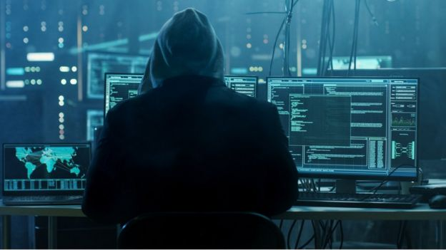Criminal hacker with multiple computer screens