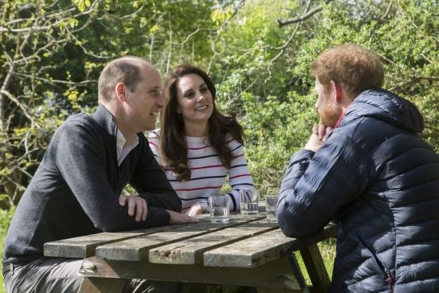 Prince William, Catherine, Duchess of Cambridge, and Prince Harry in conversation in the garden of Kensington Palace in London,