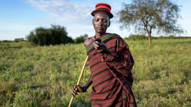Ugandan farmer looking at phone in a field