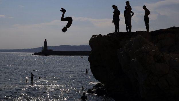 Garotos mergulhando em praia em Nice, na França
