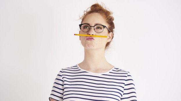 Mujer con un lápiz entre la nariz y la boca.