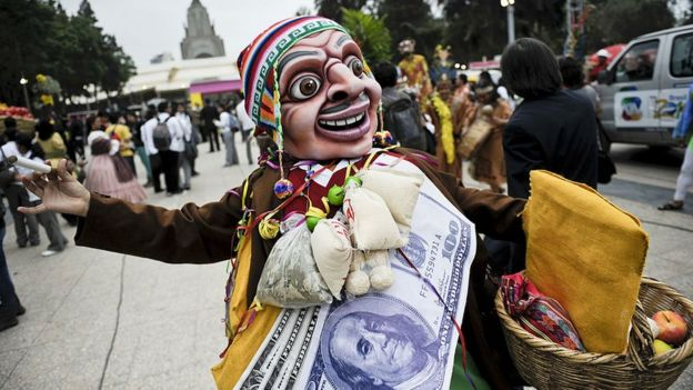 Hombre con una máscara baila. lleva al cuello un billete de 100 dólares gigante.