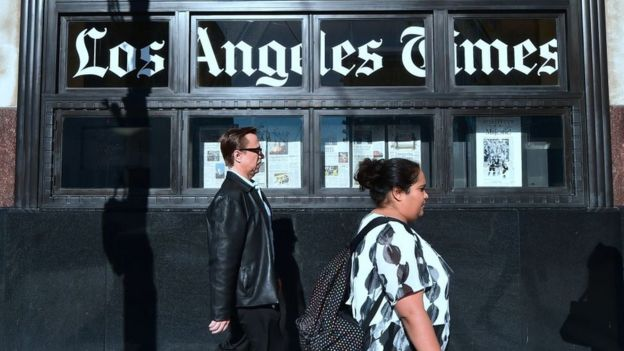 People walking past LA Times building in LA