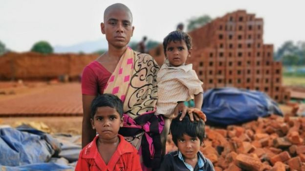 Prema standing in front of a brick kiln with her three sons