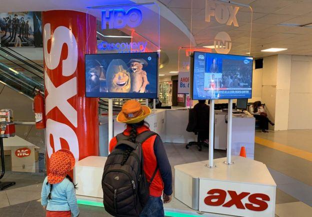 Bolivianas ante pantallas de tele isi'on