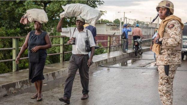Oficial de la frontera, en puente, dos personas cruzan puente