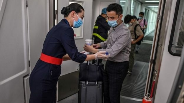 A flight attendant wearing a facemask (L) checks the body temperature of the passengers next to the door of the plane at the Tianhe Airport in Wuhan, in Chinas central Hubei province on May 29, 2020