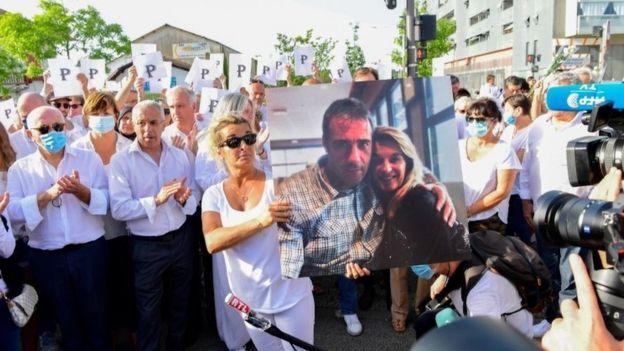 همسر راننده اتوبوس در تظاهرات در بایون فرانسه عکس همسرش را در دست دارد