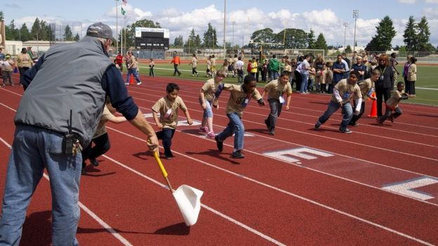 Children taking part in a race on a running track
