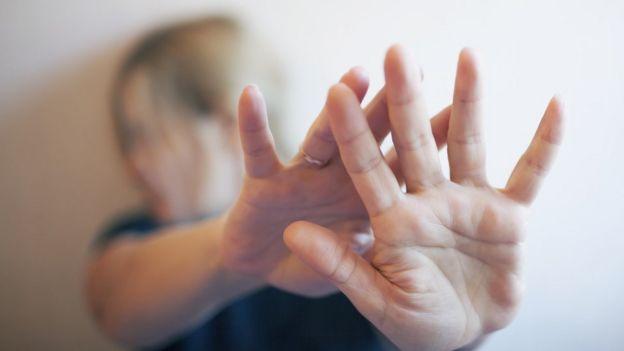 Mujer con las manos al frente.