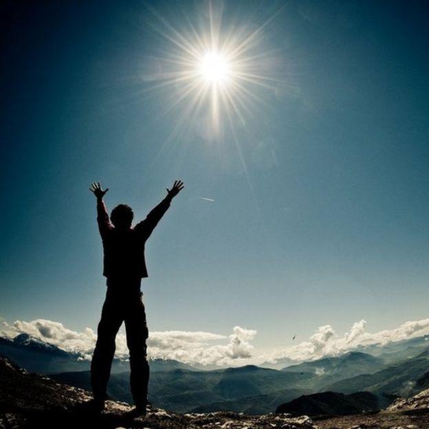 Un hombre en la cumbre de una montaña con los brazos en alto hacia el sol