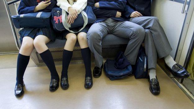 Homem sentado com pernas abertas no metrô