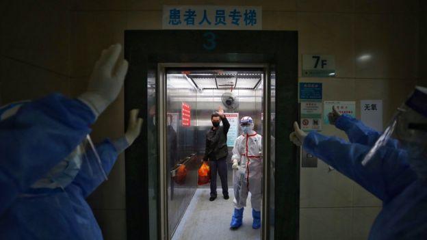 Equipe de hospital em Wuhan, na China, se despede de paciente curado da covid-19, que retribui acenos de dentro de elevador