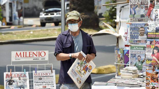 Hombre con máscara en un kiosco en la calle en México