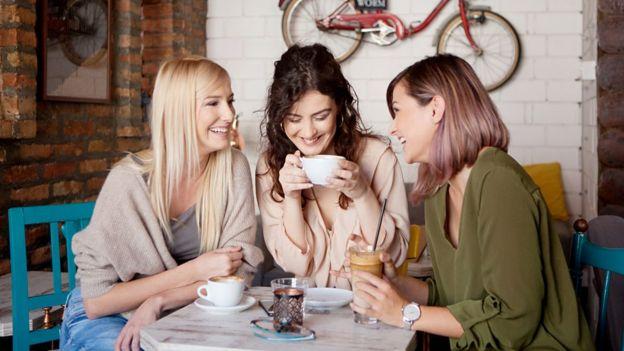 Imagem mostra três mulheres sorrindo e bebendo café ao redor de uma mesa