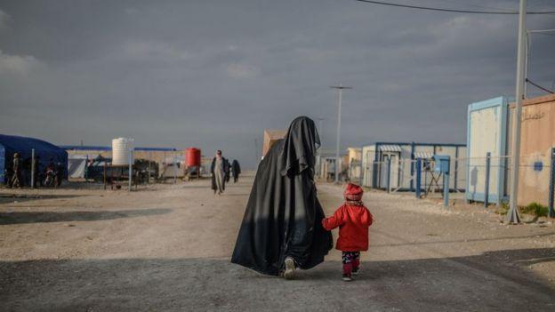 Una mujer camina junto a su niño en un campo de prisioneros.
