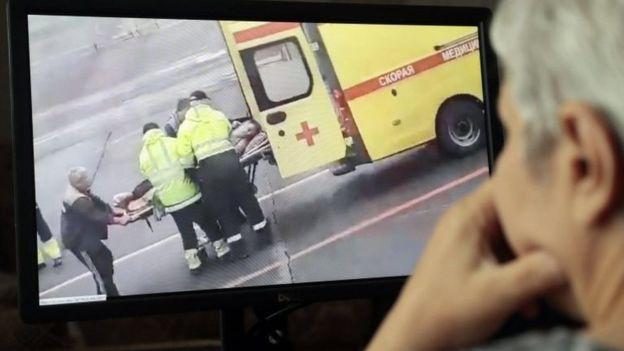 Un hombre en Moscú mira la escena del traslado al hospital de Navalny.