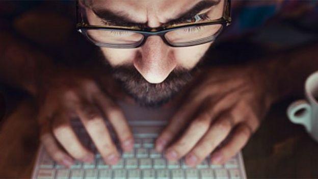 Hombre frente a la pantalla de una computadora