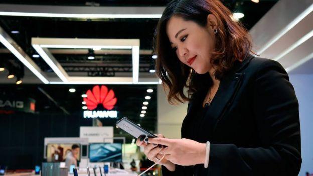 mulher olha telefone da Huawei