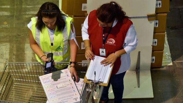 Trabajadoras del Consejo Nacional Electoral (CNE) inspeccionan los materiales de votación