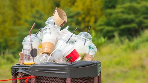 Cubo de basura con vasos de plástico de sitios de comida rápida.
