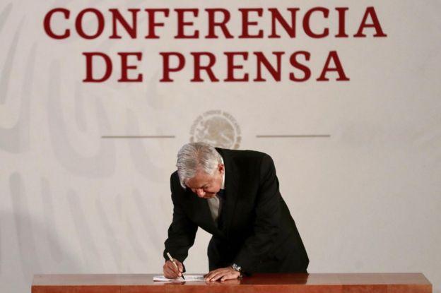 AMLO firmando el documento.