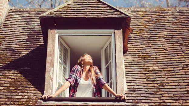 pencereden hava alan genç bir kadın