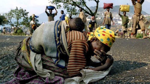 A Rwandan woman collapses with her baby on her back alongside the road connecting Kibumba refugee camp and Goma in this July 28, 1994
