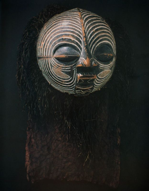 A mask of sculpted wood, pigment, hair and natural fibres.