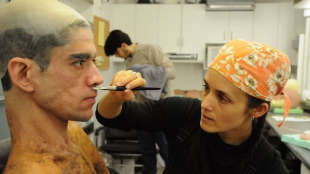 A make-up artist applies make-up to Javier's face