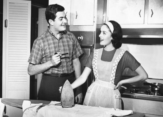 Una pareja se mira en la cocina mientras ella sujeta la plancha y él una pipa.