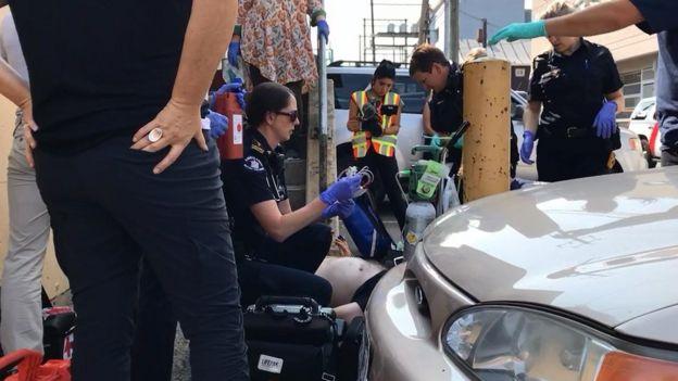 جید (نشسته با عینک) و دیگر مختصصان مرکز اورژانس، این مرد را که در بیرون یک کلینیک در بخش شرقی مرکزشهر ونکوور پس از تزریق به زمین افتاده بود با آمپول نالوکسان که اثرات فنتانیل و مواد مرفیندار را خنثی میکند نجات دادند اما او به علت صدماتی که بر اثر زمین خوردن به سرش وارد شده بود دقایقی بعد به بیمارستان منتقل شد