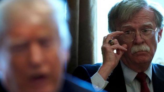 John Bolton se ajusta los anteojos mientras mira al presidente Trump