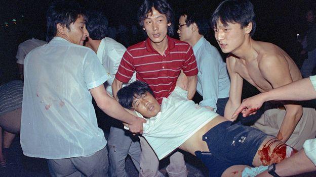 Các sinh viên đưa một người bị thương rời khỏi khu vực bị quân đội đàn áp